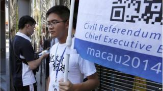 A man, left, votes on a tablet next to a volunteer with a banner promoting informal civil referendum in a street of the former Portuguese colony, Macau, Sunday, 24 Aug 2014.