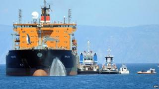 """The transfer of immigrants from the tanker """"Torm Lotte"""" to tug boat """"Grifone"""" in the middle of Messina's marine channel following a rescue operation on 20 July 2014."""