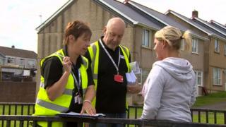 Officers from Tai Calon Community Housing speak to a tenant in Nantyglo