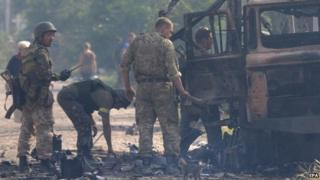 Ukrainian forces check burnt vehicles after rebel shelling, 24 Aug