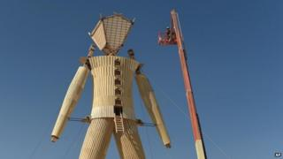 "Artists and volunteers work on the ""Man"" at the annual Burning Man event on the Black Rock Desert of Gerlach, Nevada 24 August 2014"