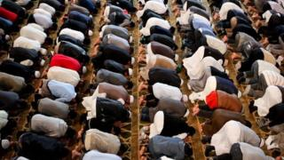 Men kneeling in prayer at a mosque