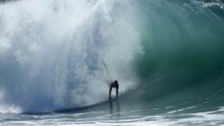 "A swimmer catches a wave at ""The Wedge"" wave break in Newport Beach, California 27 August 2014"