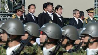 "This file picture taken on 27 October 2013 shows Japanese Prime Minister Shinzo Abe (top centre) inspecting troops of Japan's Self-Defence Force during a military review at the Ground Self-Defence Force""s Asaka training ground, suburban Tokyo"
