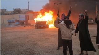 Anti-government protesters in front of burning police vehicle in Ramadi (file photo)