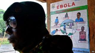 A soldier from the Sierra Leone army stands near an Ebola information poster outside Kailahun, on August 14, 2014.