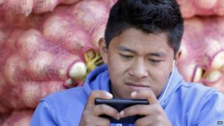 A young man texts at a market in Quito as government prepares to introduce electronic currency