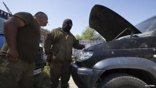 Armed pro-Russian separatists inspect a damaged car in the southern coastal town of Novoazovsk