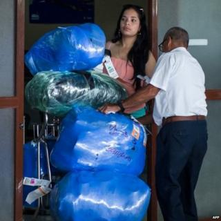 An airport worker checks large bundles carried on a cart by a woman at Havana's airport. Photo: August 2014
