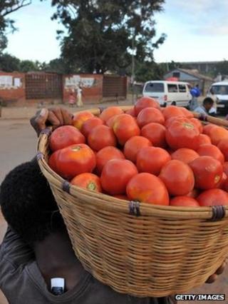 Market vendor carrying basket of fruit (Getty Images)