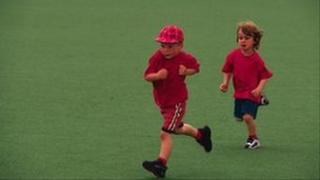 Two children running across playing field