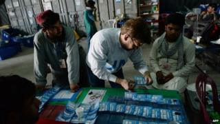 "Afghan election commission workers sort ballot papers during an audit of the presidential run-off vote in the country""s general election at a counting centre in Kabul on August 25, 201"