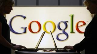 Google logo in background of two people on laptops