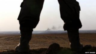 An Iraqi Kurdish Peshmerga fighter holds a position as smoke billows on the front line in Khazer, 40 km West of Irbil, in northern Iraq on 16 September 2014.