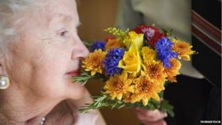 person smelling flowers