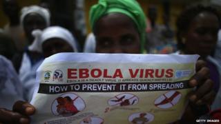 Woman holding up Ebola information poster
