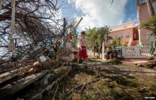 Stefano Ausenda shovels debris away from his driveway after Hurricane Gonzalo passed through in Sandys Parish, western Bermuda, October 18, 2014