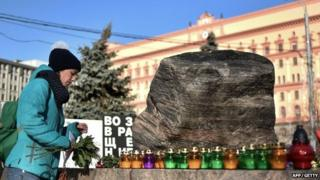 A woman places a candle and flowers at the memorial to the victims of Soviet-era political repression at the Solovky Stone monument, on Lubyanka Square in Moscow.
