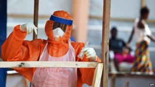 A health worker wearing a personal protective equipment works on 11 November 2014 outside Freetown
