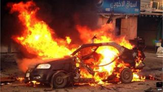 A blaze engulfs a car at the scene of an explosion in the Shiite Muslim Al-Amin district of Baghdad, 8 December 2013