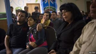 Undocumented immigrant Angela Navarro and her husband Ermer Fernandez (L), along with other immigrants and supporters, watch U.S. President Barack Obama speak 20 November 2014