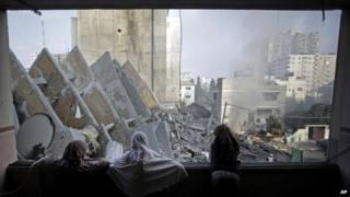 A Palestinian family looks through a window at the remains of the 13-storey al-Basha Tower in Gaza City (26 August 2014)