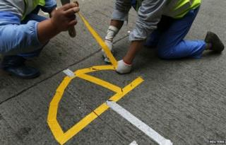 """Workers remove a logo left by pro-democracy protesters in the shape of an umbrella during a clearance at the last """"Occupy"""" protest site blocking a main road at Causeway Bay shopping district in Hong Kong"""