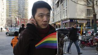 Yang Teng holds up a statue depicting a goddess of justice and a rainbow colour flag as he arrives to attend a court verdict in Beijing, China, Friday, Dec. 19,