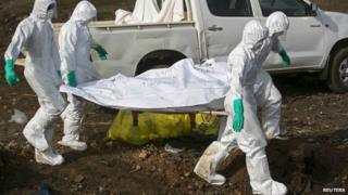Health workers carry the body of a suspected Ebola victim for burial at a cemetery in Freetown December 21, 2014.