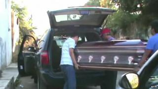 Father Gregorio Lopez's coffin is loaded into a hearse