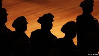 New York police officers stand in silhouette.