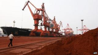Bulldozer scoops soil containing various rare earth to be loaded on to a ship in China