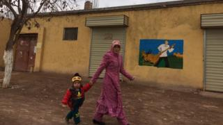 A woman and child walk past a building with a mural painted on its side