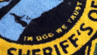 A rug in a US sheriff's office mistakenly reading 'in dog we trust'