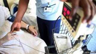 A nurse takes a patient's temperature