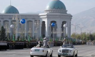 Officials in white cars at a military parade in Ashgabat
