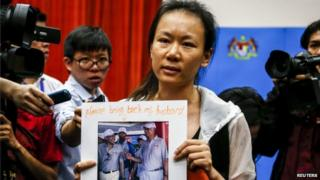 The wife of a passenger aboard the missing Malaysia Airlines Flight MH370, holds a picture of her husband, at a news conference in Putrajaya, 29 January 2015