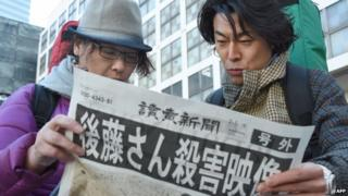 People read special edition of newspaper in Tokyo, after announcement of Kenji Goto's death