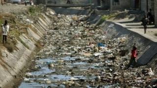 Haitian boys launch kites inside a refuse-strewn sewer canal in Cite Soleil, Port au Prince, Haiti