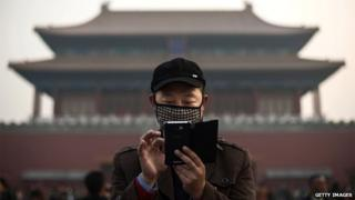 A Chinese man wears a mask to protect against pollution as he uses his smartphone on a hazy day outside the Forbidden City 20 November 2014 in Beijing, China