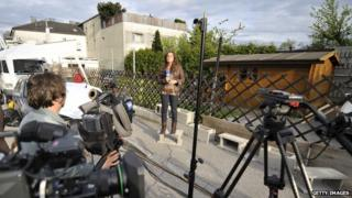 A Spanish journalist does a piece to camera in front of the house where Josef Fritzl lived, in Amstetten, in May 2008.