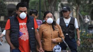 People walk with face masks due to ashes from the Fuego volcano in Antigua Guatemala, Sacatepequez departamento, 45 km southwest of Guatemala City on Febrary 7, 2015.