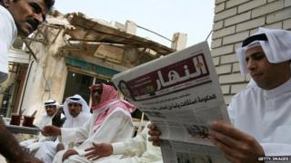 A Kuwaiti man reads a local newspaper amongst friends