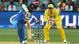 "India's Shikhar Dhawan (L) plays a shot as Australia""s Brad Haddin (R) looks on"