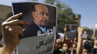 A protester holds up a poster of Yemen's former president Abd-Rabbu Mansour Hadi during an anti-Houthi demonstration in Sanaa