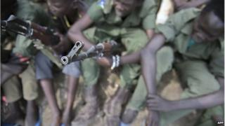 Child soldiers sit with their rifles at a ceremony of the child soldiers disarmament, demobilisation and reintegration in Pibor overseen by UNICEF and partners on 10 February 2015