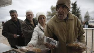 People receive food handouts in Athens on Monday