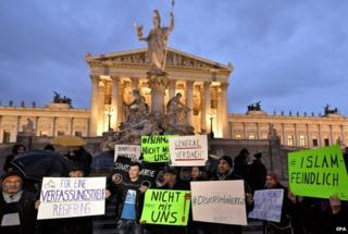 """Protesters hold banners during the demonstration under the slogan """"New Islam Law? Not with us!"""" in front of the parliament building in Vienna, Austria, 24 February 2015"""