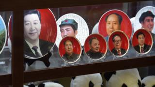 Decorative plates featuring Chinese leaders (L-R) current President Xi Jinping, Mao Zedong, Deng Xiaoping, Jiang Zemin and Hu Jintao are seen above a row of Pandas in a shop window in Beijing
