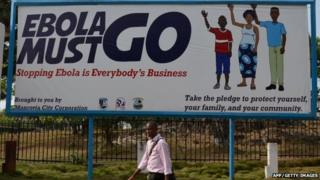 "A man walks past an Ebola campaign banner with the new slogan ""Ebola Must GO"" in West Africa on 23 February 2015."